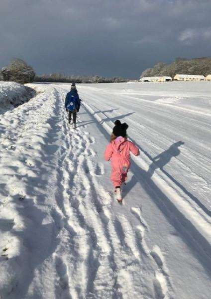 Isla, in pink, and Archie Gooderham on their way to school through the snow at Stanton'Picture: Geniene Gooderham