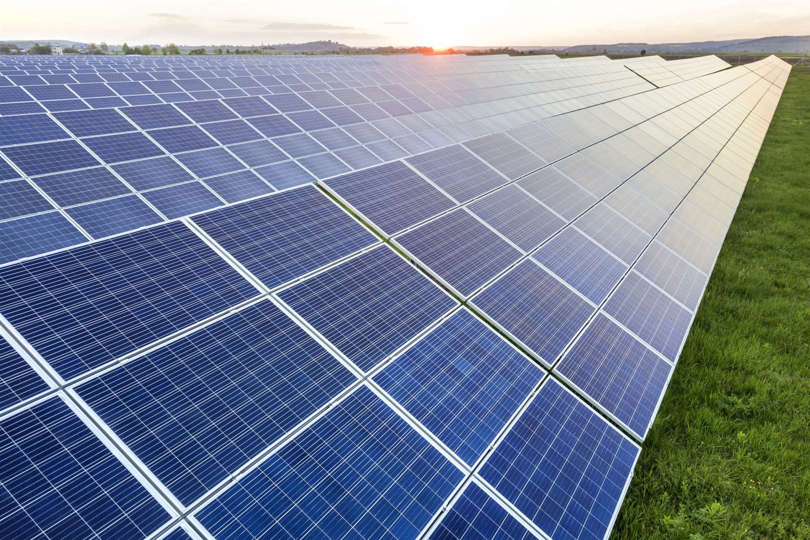 Blue solar photo voltaic panels system producing renewable clean energy on rural landscape and setting sun background. (Blue solar photo voltaic panels system producing renewable clean energy on rural landscape and setting sun background., ASCII, 119 (43101796)