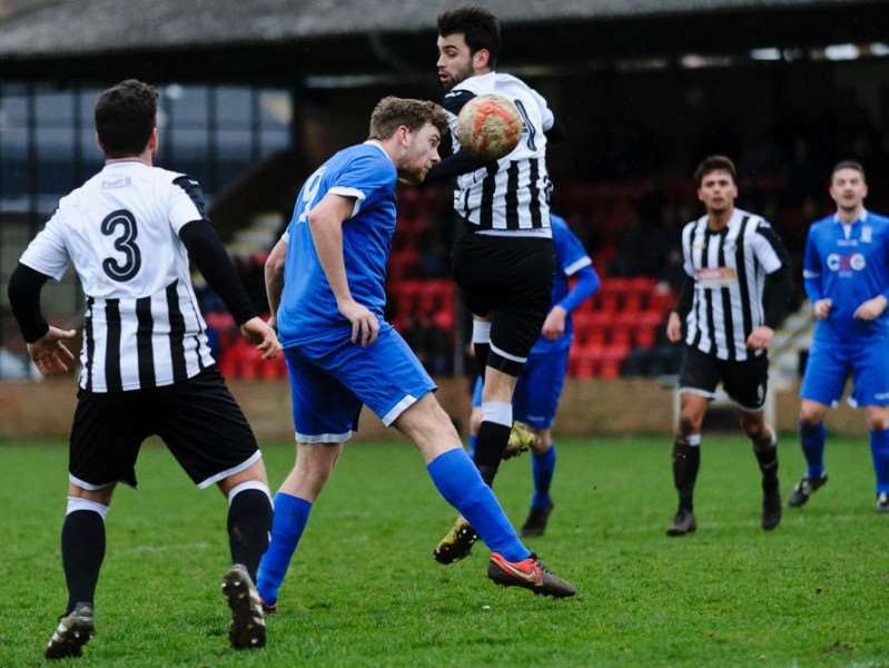 Charlie Holmes heads the ball for Haverhill Borough