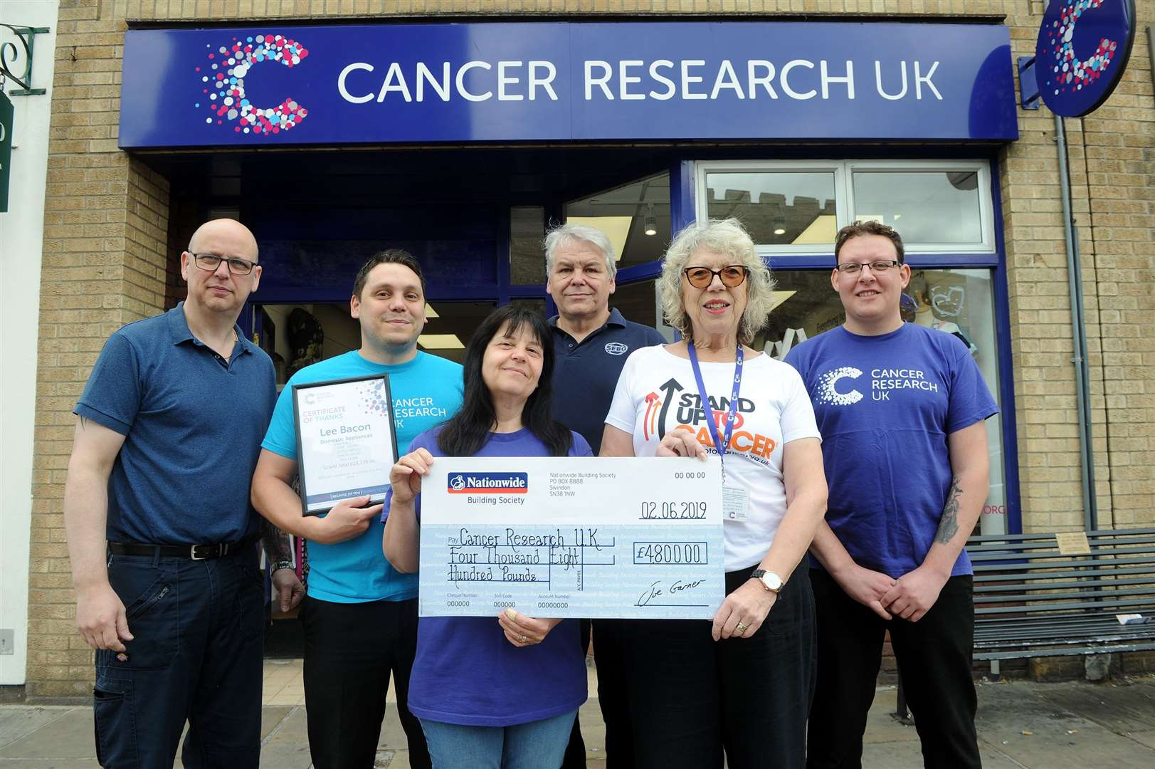 Domestic Appliances in Sudbury is handing over a cheque for £4,800 to Cancer Research UK, which was raised during a charity football match...Pictured: Phil Wood (Manager at Cancer research UK Sudbury), Lee Bacon (Domestic Appliances Manager), Karen and Neil Bacon (Director), Ivy Pond (Volunteer fundraiser at Cancer Research UK Sudbury) and Shane Johnson (Colleague at Domestic Appliances) ...PICTURE: Mecha Morton. (13842104)