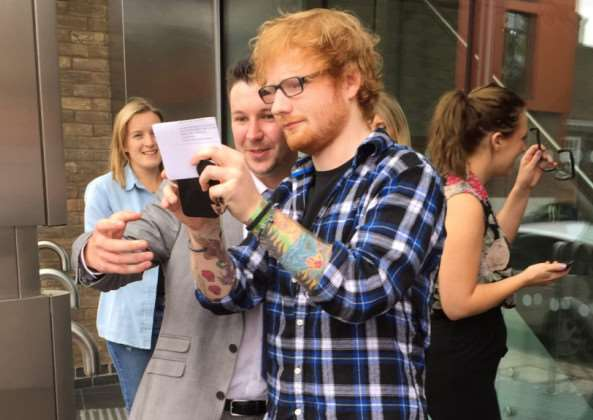 These pictures show Ed Sheeran walking out of a driving theory test centre with a massive smile on his face as he clutches his test results. (Picture: Mark Rothwell / SWNS)