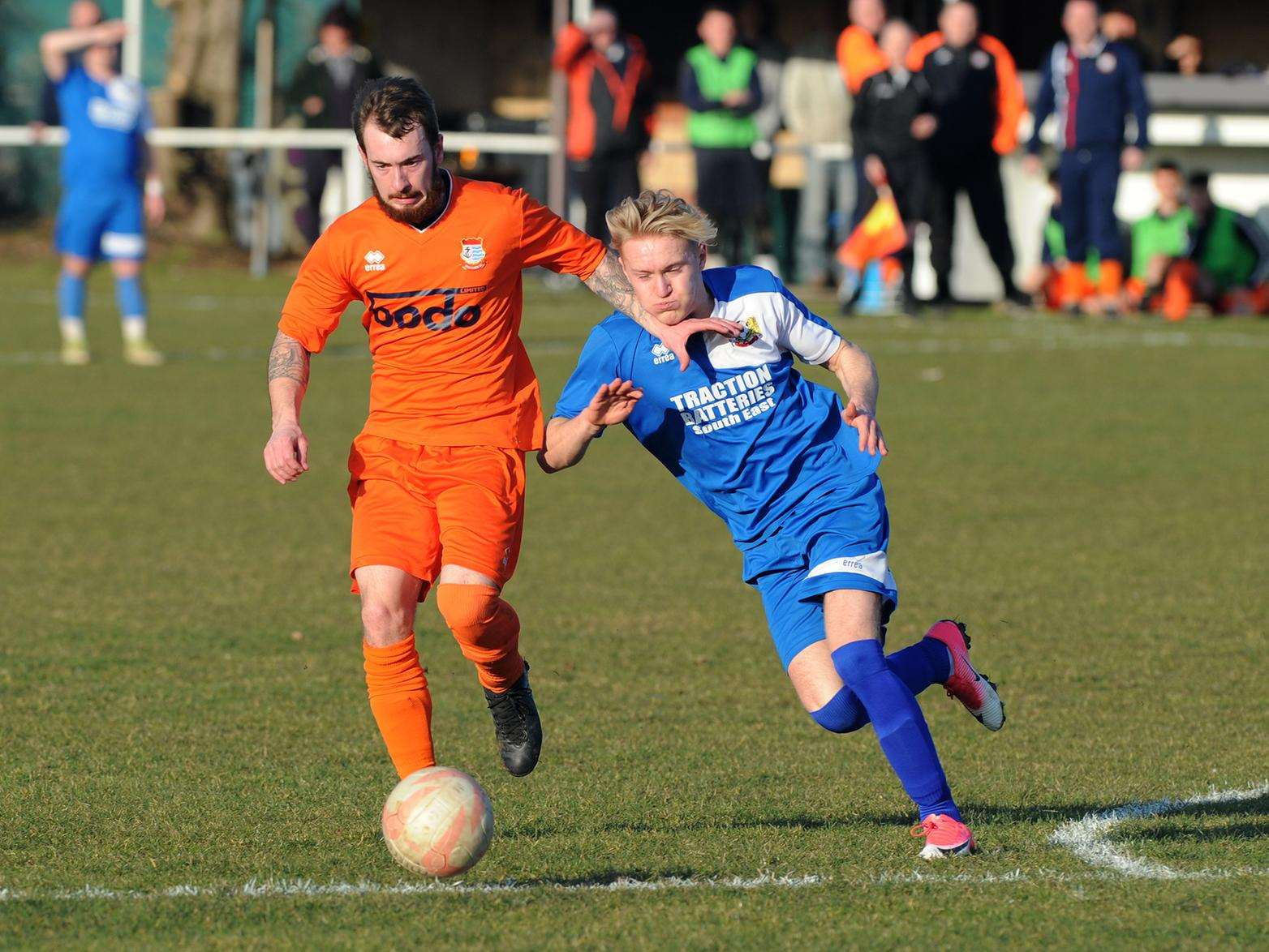 HELD OFF: Stephen Vincent (Diss - Orange) holds off the tackle of Rocha Foster (Cornard Utd - Blue) (Picture: Mecha Morton)