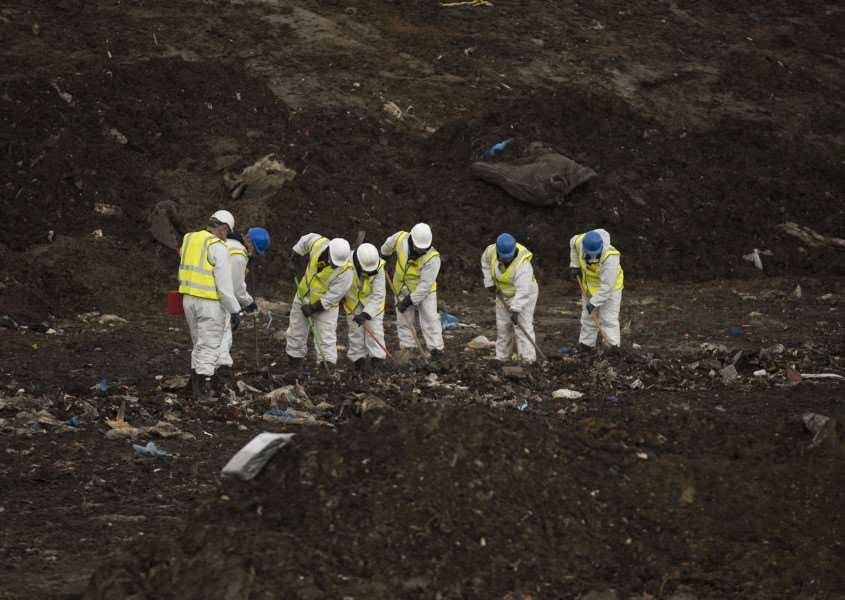 Police search teams sift through batches of rubbish dug out of the tip by machines