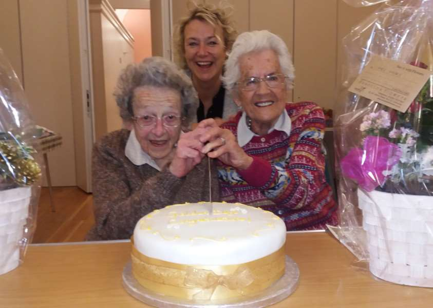 The Golden Days Club's organiser Joyce Talboys, left, and chairwoman Elsie Wicks cut the cake watched by Sue Szymanski, the St John's Centre's community development manager ANL-161212-165622001