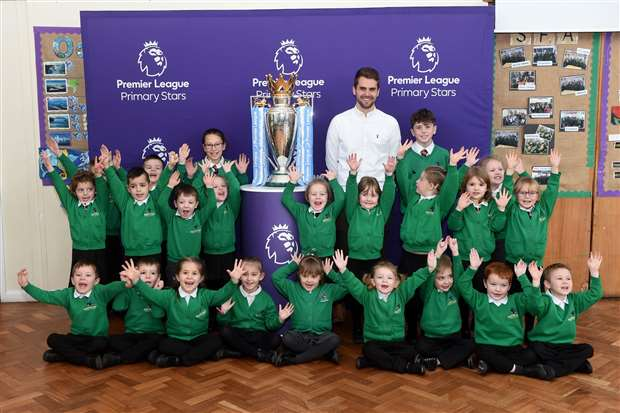 Year 6 teacher and PE Lead Chris Boyd, head boy, head girl and Scotland Class, with the Premier League trophy. Picture by Mecha Morton
