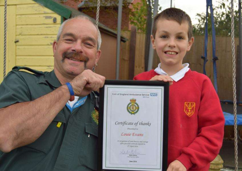 Louie Evans is presented with his certificate by paramedic Pete Edwards