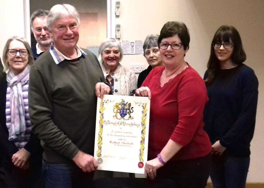 Richard Mortlock, with community association trustees, receives the scroll of honour from Cllr Diane Hind