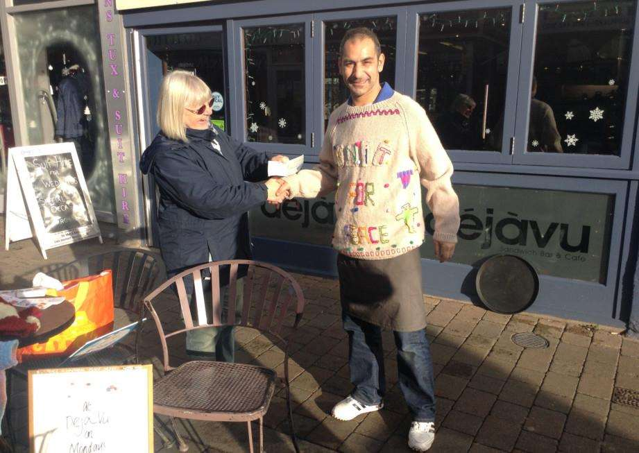 Chris Heart receives a cheque for �100 from Harry Zachariou at Deja Vu for Knit for Peace ANL-141229-113017001