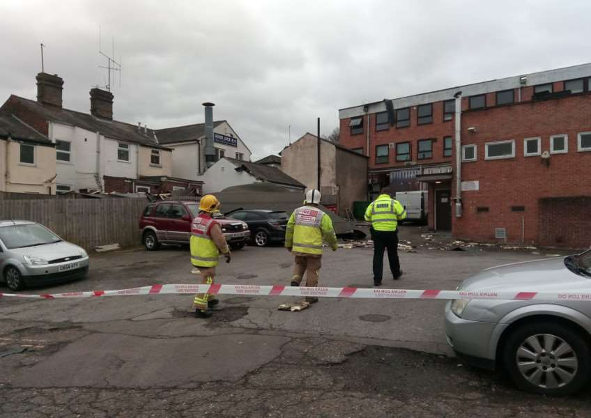 Police anfd fire officers inspect the damage after the roof covering on Heron House had blown off. Most of the covering can be seen on top of the black Astra in the picture. Picture by Steve Barton