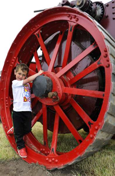 Hockwold Country Fair'Bailey Nuss (4) taking a close up look at this 1907 Burrell Agricutural Traction Engine wheel at the fair ANL-150614-174455009