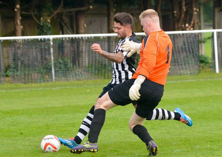 GAME ON: Dan Smith, who scored Melford's second goal, tries to take the ball around Thetford keeper Nick Parr
