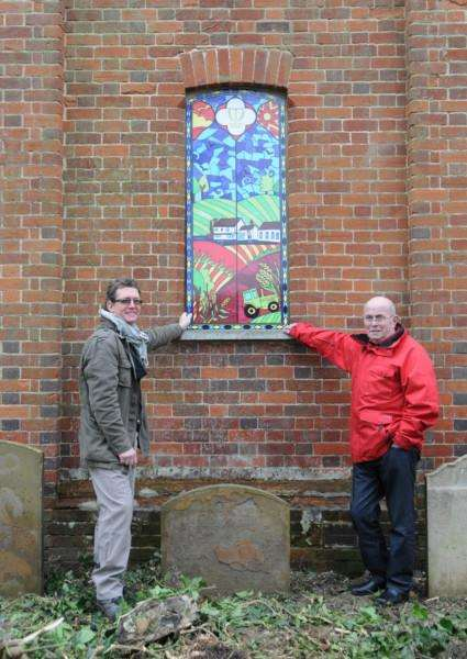 Haverhill in Bloom chairman Ben Pumfrey (left) and secretary Tim Marks with one of the artworks in the window recesses in St Mary's Churchyard ANL-141121-143644005