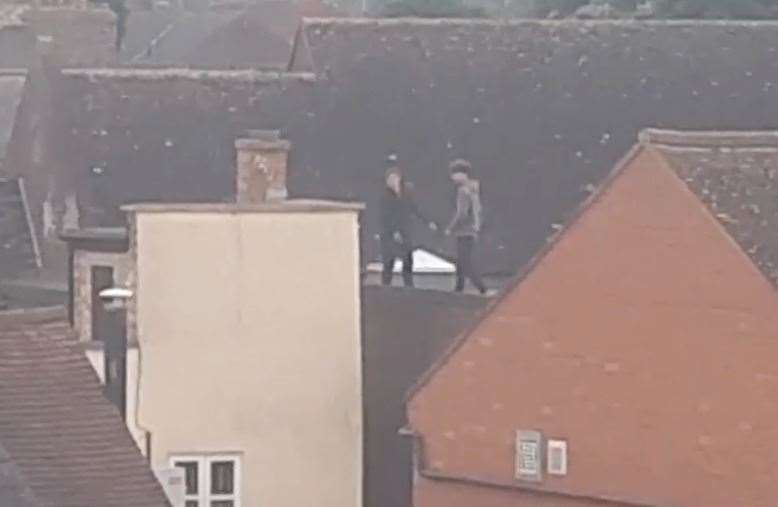 Teenagers climbed across roofs near Newmarket's High Street today (12587601)
