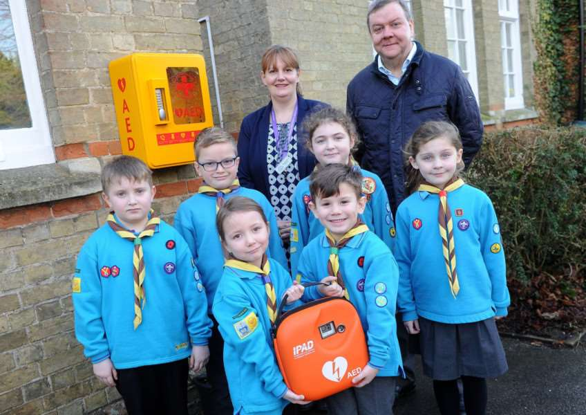 Some of the Beavers with a defib, Lakenheath Primary School head Sally Esom and Mike Rowntree who helped with the fundraising. Picture; Mecha Morton