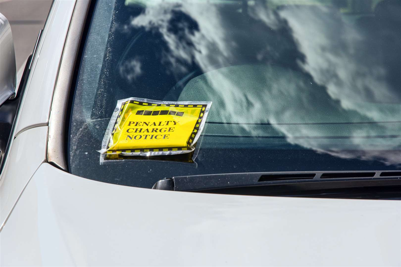 A Parking Ticket also called a Penalty Charge Notice glued to a car windscreen. The yellow ticket is the official notice issued by the Local Authority Traffic Warden for a vehicle which is contravening a parking restriction or regulation. (21196680)