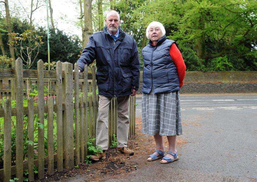 Andrew and Anne-Marie Hill next to one of the drains, which has been causing flooding to their home for years. Picture: Mecha Morton.