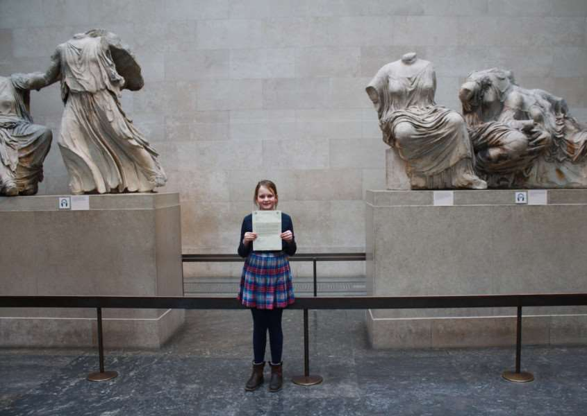 Freya Clayton holds her letter from Jo Churchill next to the Elgin Marbles at the British Museum ANL-161203-102423001