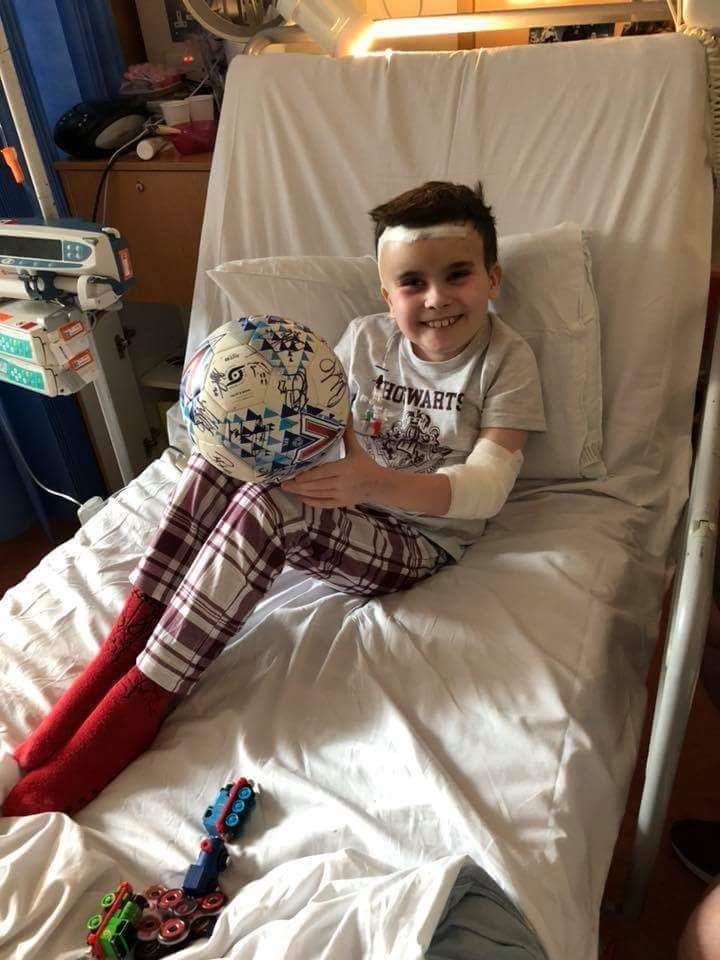 Cayden Le Roy-Tickner in hospital with a football signed and presented to him by Cambridge United players (2327248)