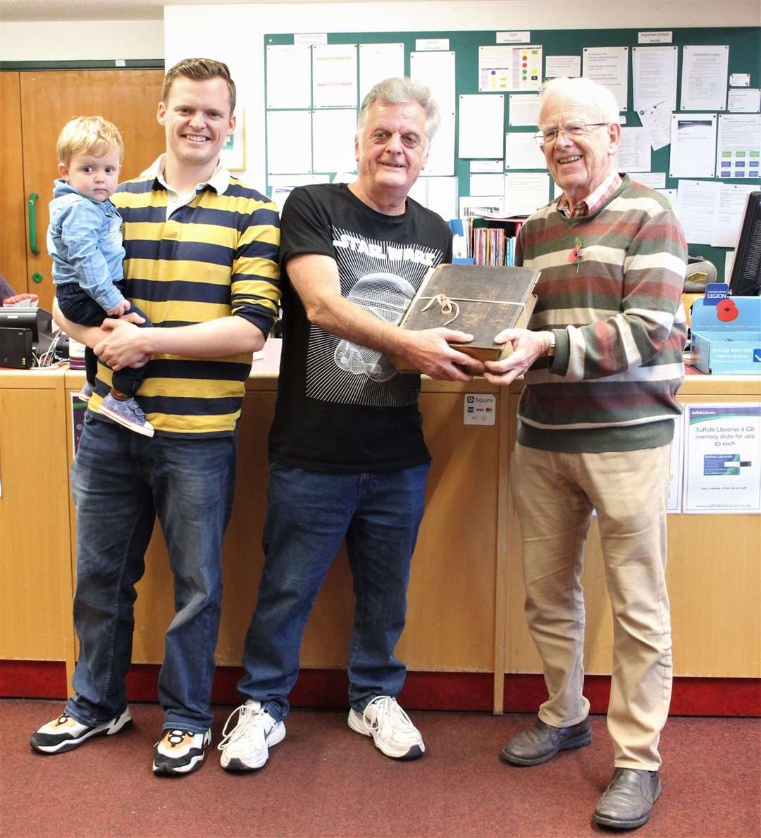 Alan Bumpstead (right) of the Haverhill Family History Group, presents the Peck family bible to Robert Scrivener, his son James and grandson Isaac. Contributed picture