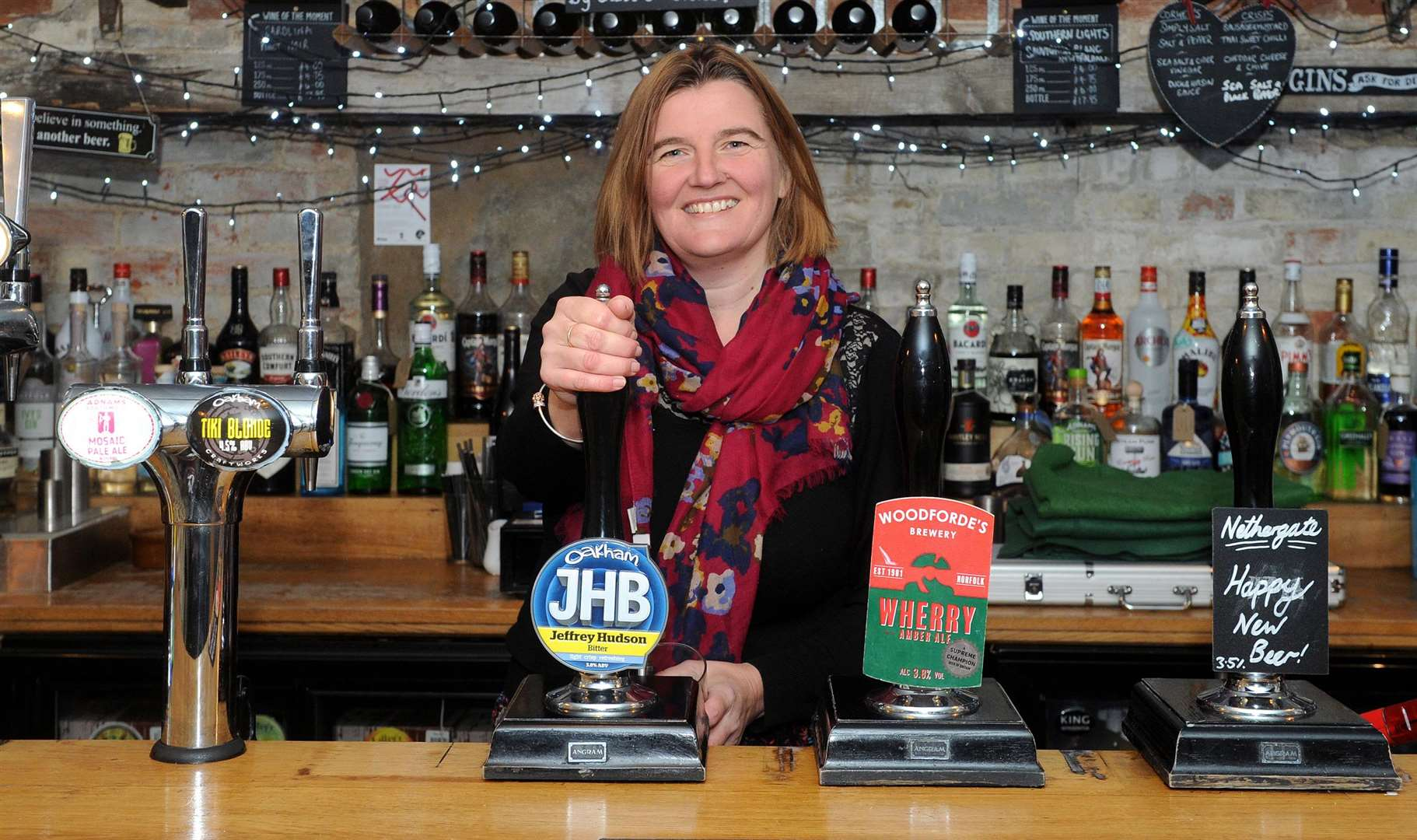 Heather Warren pulls a pint behind the bar at Oakes Barn