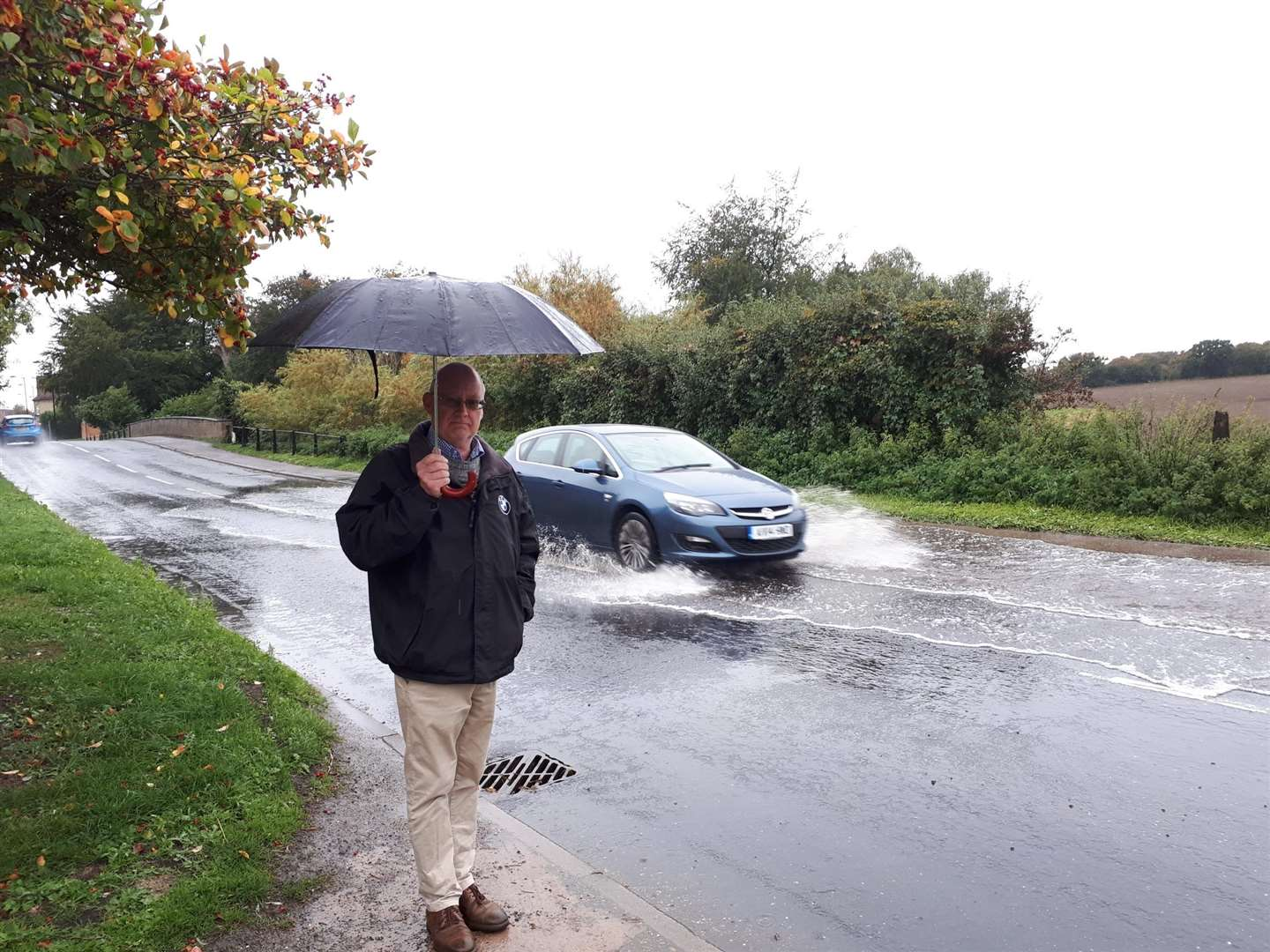 Cllr John Nunn, parish and district councillor for Long Melford, overlooks flooding in Hall Street, caused by a recurring blocked drainage issue. Submitted picture. (4527844)