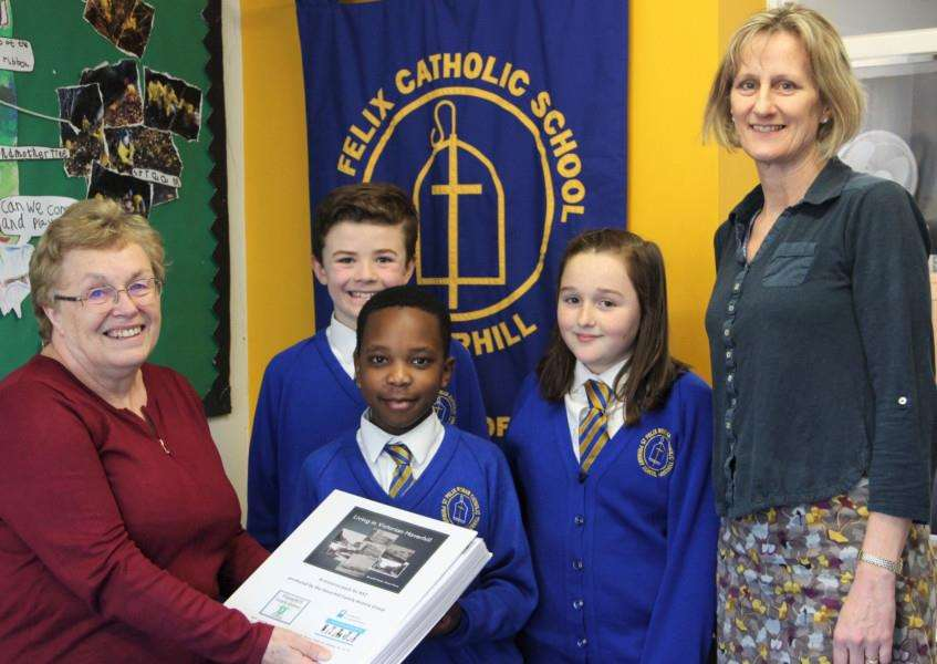 Haverhill Family History Group member, Charmian Thompson, presents the resource pack to St Felix RC Primary School pupils and KS2 leader Claire Shirm.