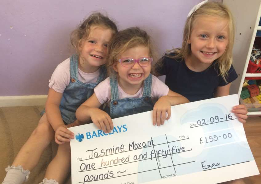 Emma-Louise Lovegrove presents her cheque to Jasmine Moxam, centre, and her twin sister Summer ANL-160709-161846001