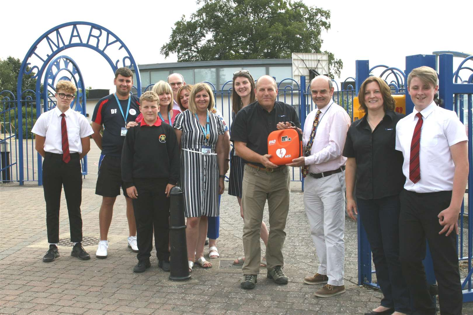 Emma and Steve Murrow and family hand St Mary's head Colin Haley the defibrillator (3449379)