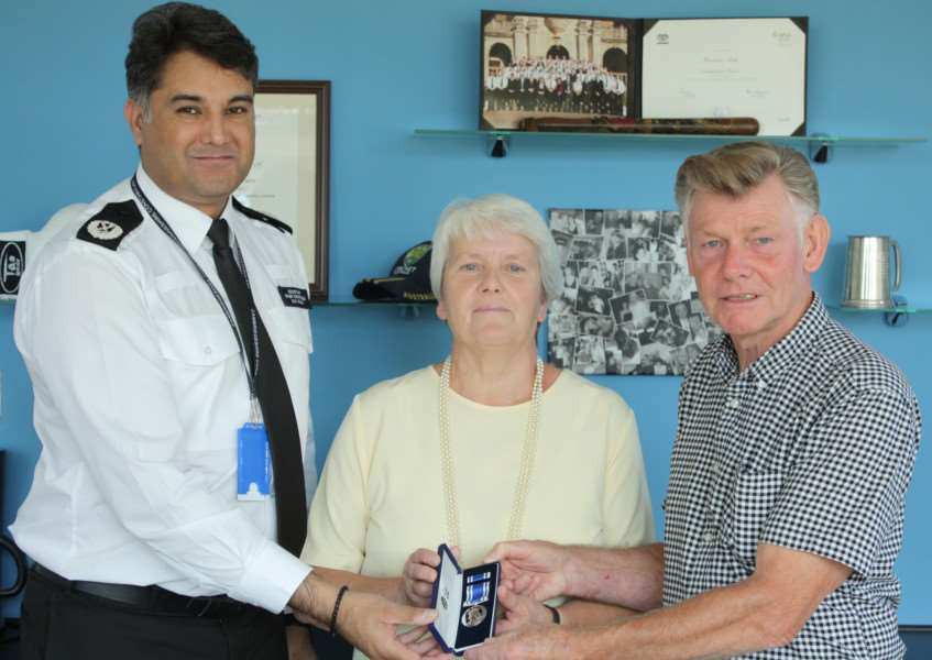 Paul and his wife Christine presented with the medal by Assistant Chief Constable Nav Malik