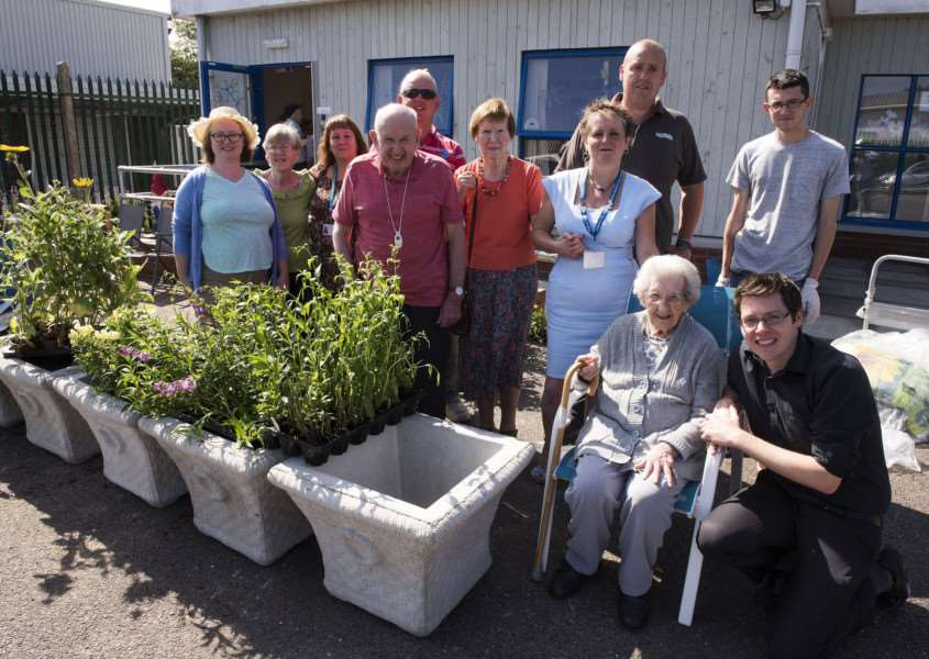 Matt Moss, Paul Sheppard and Karol Holtyn, from Poundfield Products, present planters to Gatehouse, in Bury St Edmunds, to replace others which were stolen. They are pictured with Elaine Channen, the charity's dementia hub facilitator, and clients. Picture: Mark Westley.