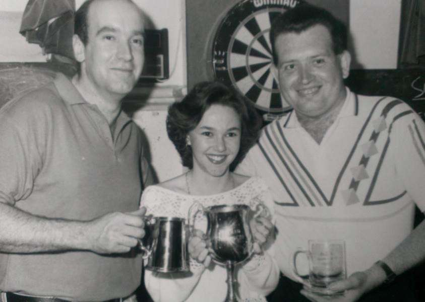 Can you tell us anything about this trio who appear to be collecting darts trophies in this photo from yesteryear?