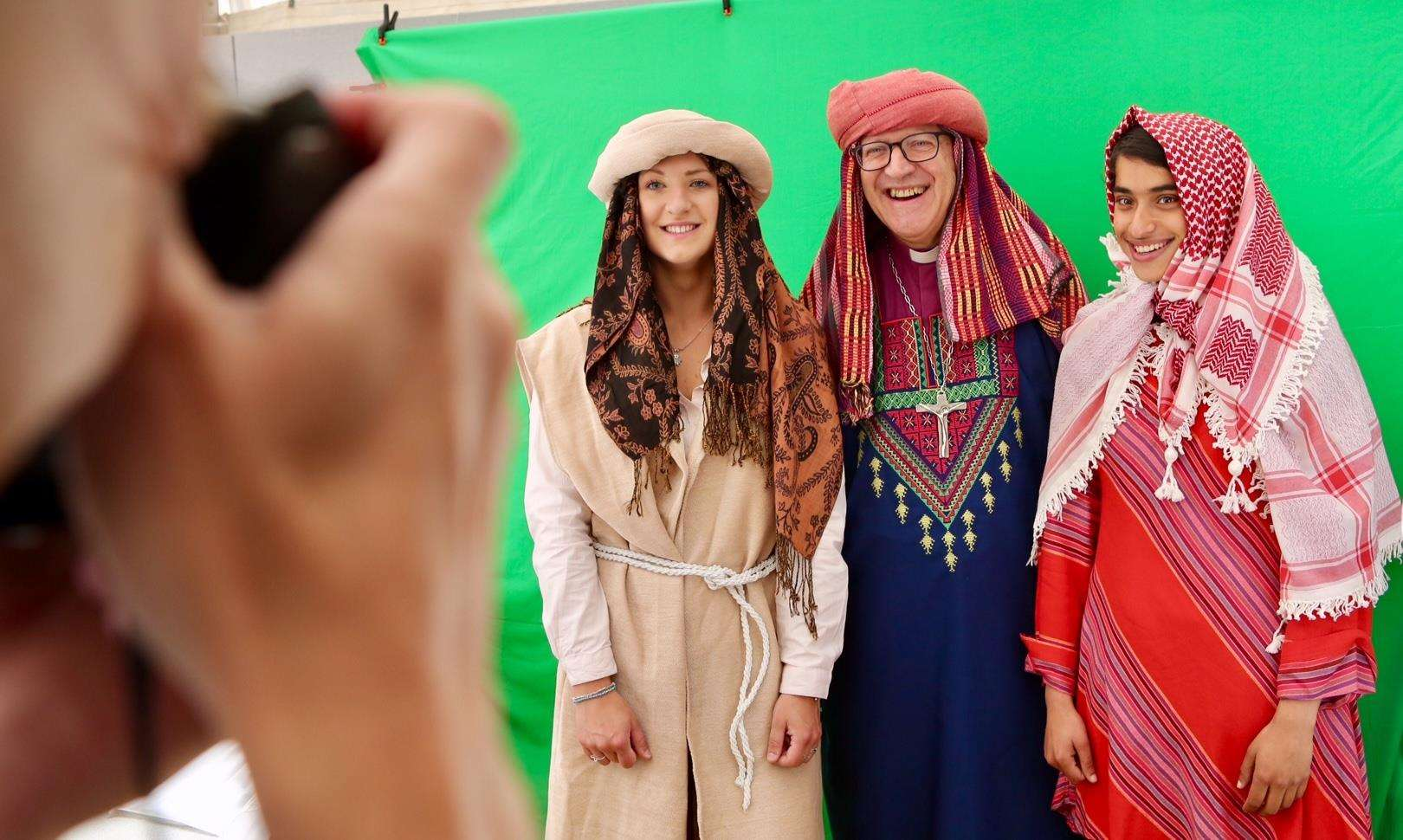 Bishop Martin Seeley at the Suffolk Show Church of England marquee with Amber Rudland, left, and Annika Mathews, right, robed up in the fun photo booth area. (2285214)