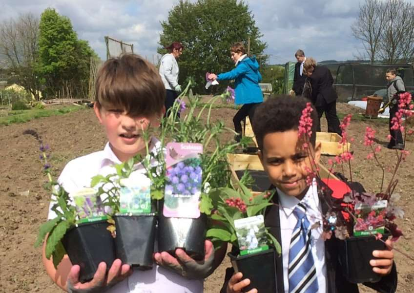 Castle Manor pupils Luke McElarney and Chi Khan lend a hand to help develop the sensory garden