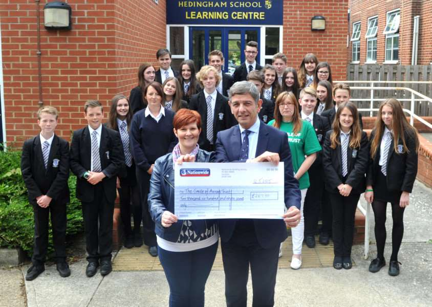 Hedingham School and Sixth Form presented a cheque of all the money raised by the school, individual children and other individuals from the community for the Smile of Arran Trust in memory of Arran Tosh who died last year from a brain tumour.''Pictured: All those involved, along with Alison Tosh receiving the cheque from John Panayi (Head Teacher) ANL-151205-171454009
