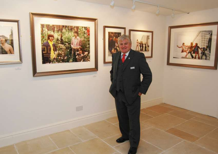 Tom Murray with some of his iconic Beatles photos being exhibited at the new offices of Jacobs Allen Chartered Accountants