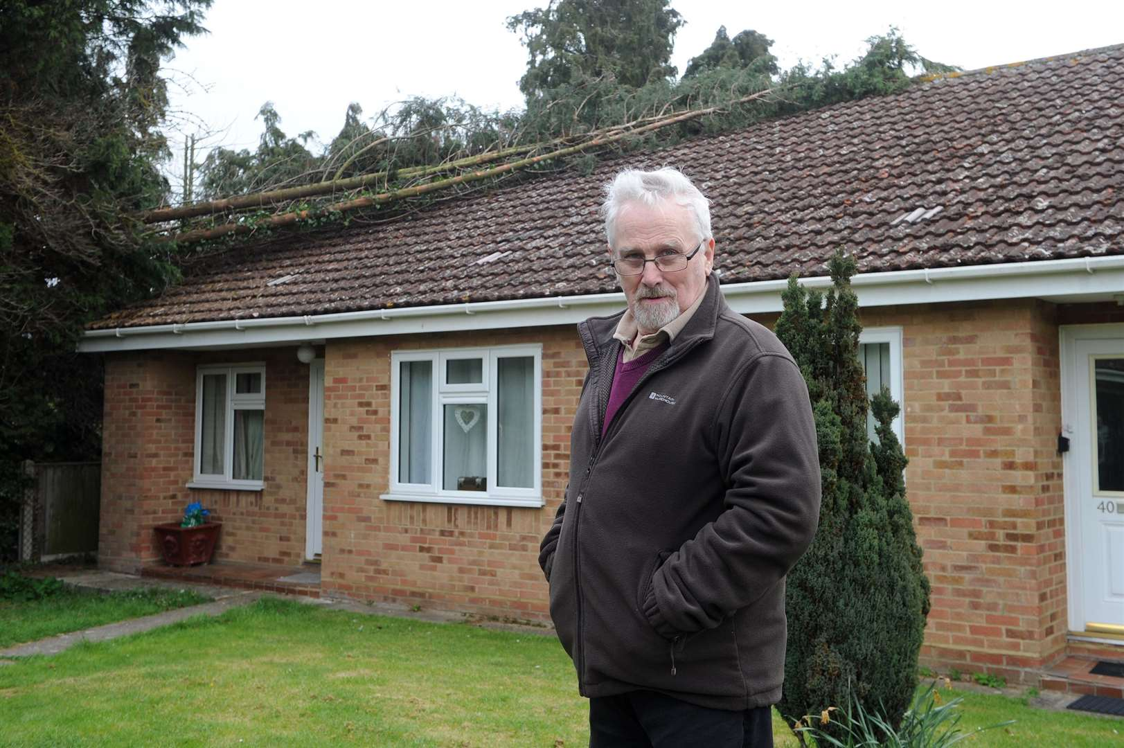 Alan Crank stands near the piece of fallen tree on the bungalow, in Britten Avenue, Stowmarket Picture by Mecha Morton