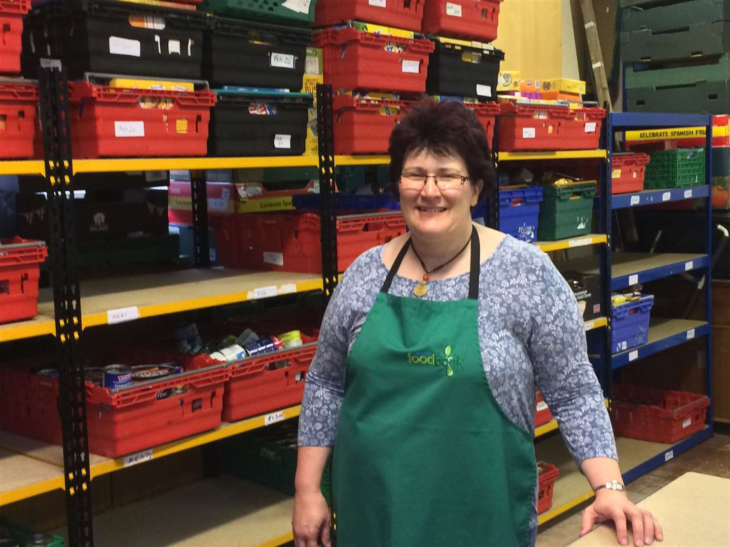 Manager Ali James in front of the shelves of Thetford Foodbank