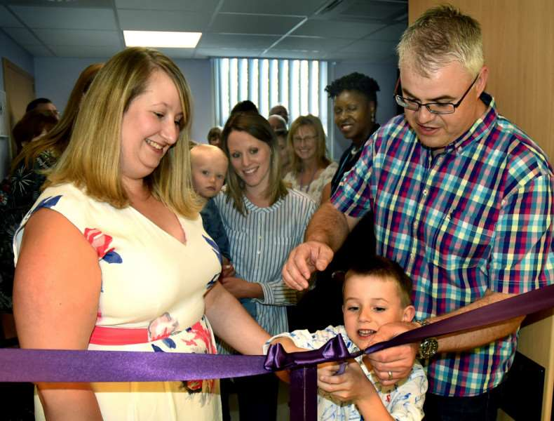 Jo and Paul Rayner and their son Thomas cutting the ribbon to open the room
