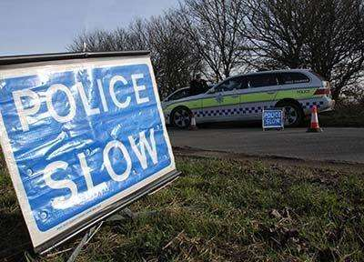 A police slow sign at a crash scene