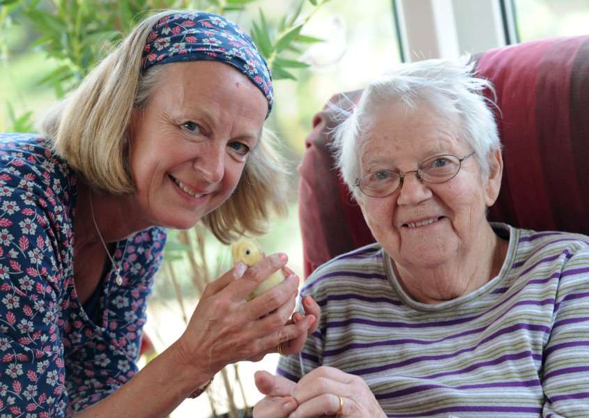 Risby Park care home manager with resident Betty Philips and duckling