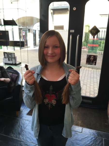 Ella Johnson, 12, had her hair cut as part of hairdressing student Sarah Picken's charity event ANL-161204-162246001