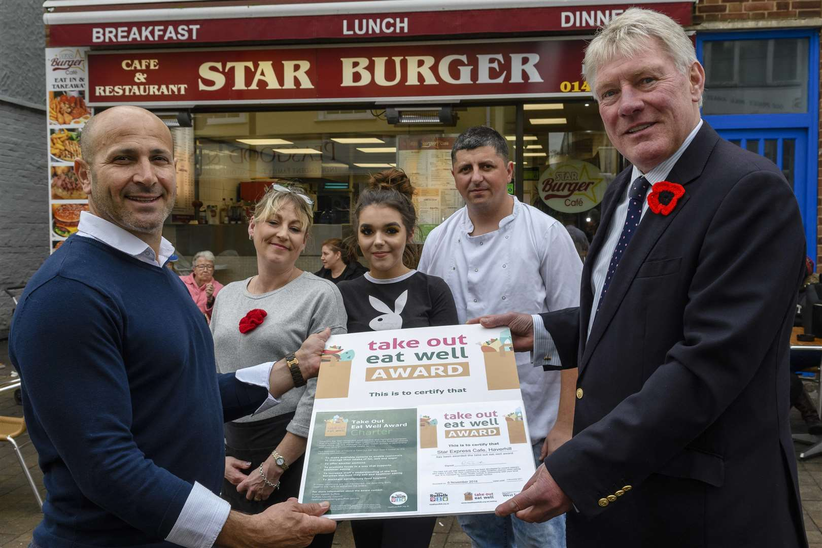 Haverhill, Suffolk, UK, 06 November 2018..Cllr John Griffiths (right) of St Edmundsbury awarding the first Council Take Out Eat Well Awards in West Suffolk which recognises takeaway food businesses that offer healthier food choices, to Ali Yagir Star Burger on Queen Street, Haverhill with staff behind from left Julia Bridgeman, Katie Battersby and Omer Sadik...Picture: Mark Bullimore Photography. (5258609)