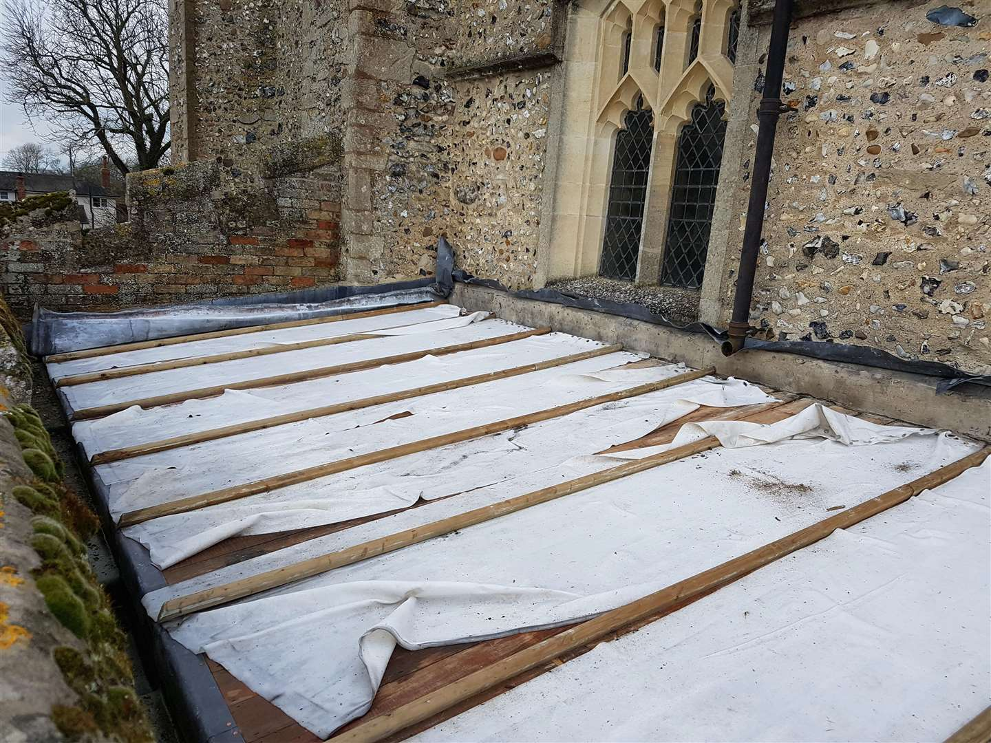 Desecrated: Plastic sheets replace the stolen lead to protect the interior of Wood Ditton Church from the elements.