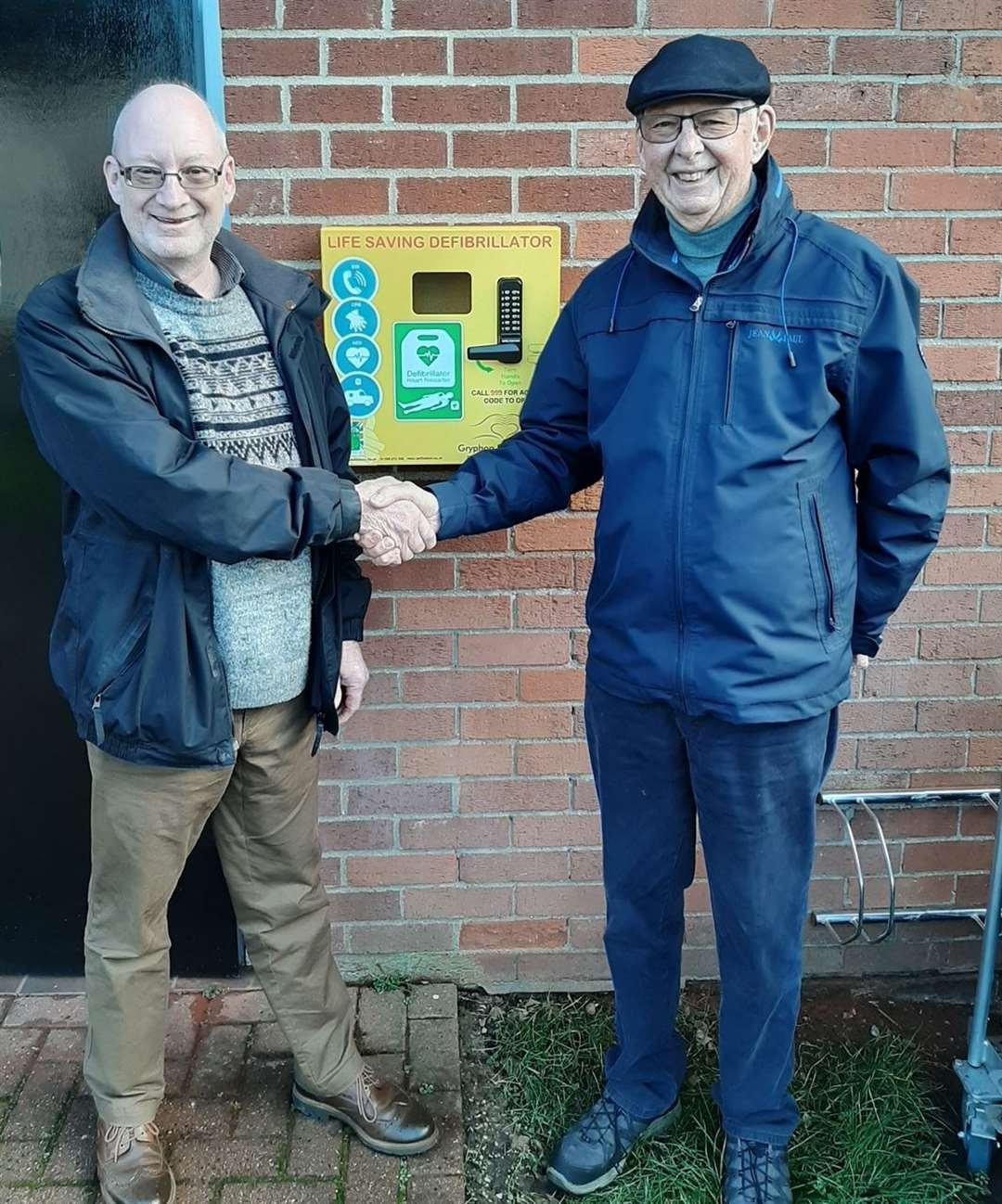 Long Melford Parish Council chairman John Nunn and local resident Robin Hughes at the new defibrillator in Cordell Road. Picture: Contributed. (25824537)