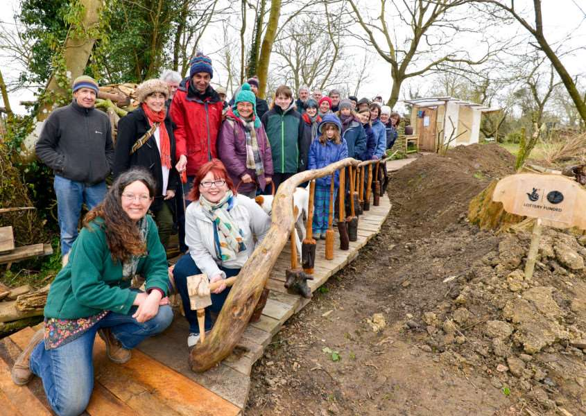 Opening of the Orchard Board Walk at Orchard Barn in Ringhsall. Sarah Partridge from Orchard Barn (kneeling left) with Karen Cannard from The Rubbish Diet who opened the bridge along with all of the volunteers who helped to create the bridge. ANL-150322-165714009