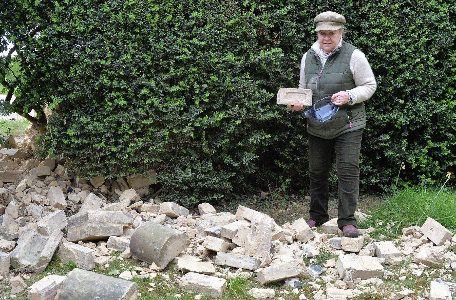 Picking up the pieces yet again ... Victoria Coldrey surveys the damage to her wall after it was hit by a car
