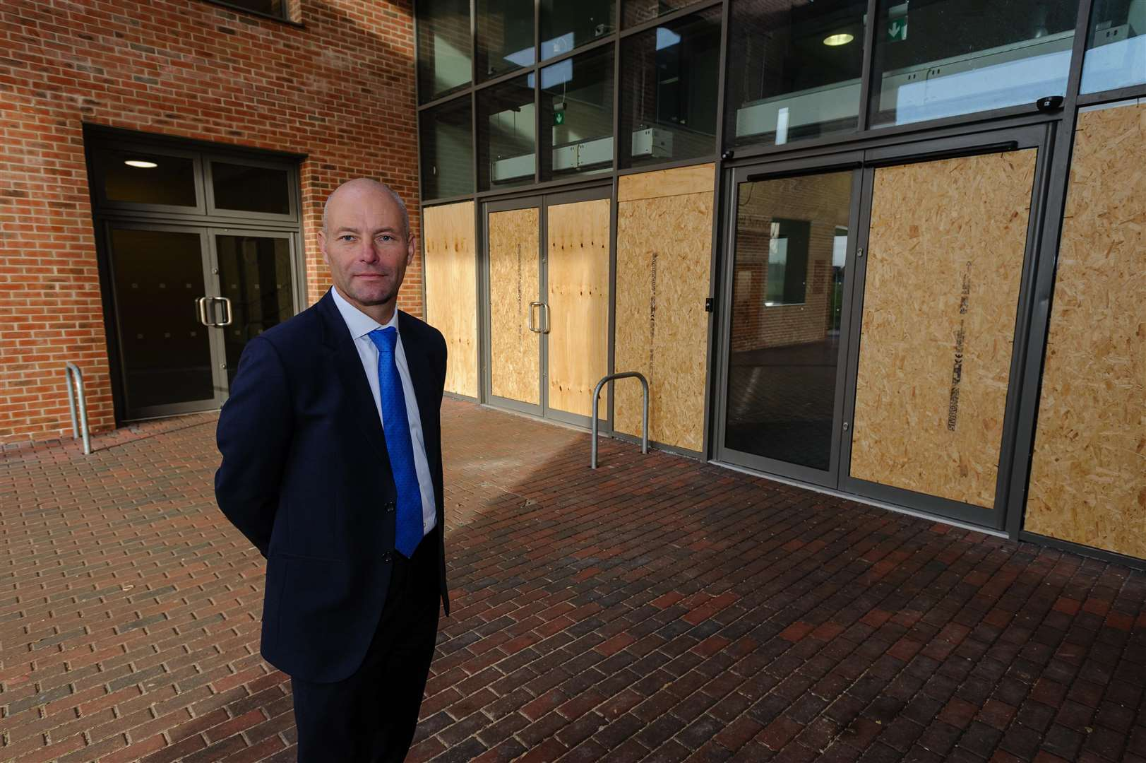 Vandals have smashed the glass doors at Thomas Gainsborough School, resulting in thousands of pounds in damage. The windows to the students' entrance were smashed on three separate incidents at the weekend. Pictured is Headteacher Wayne Lloyd...Picture by Mark Bullimore Photography. (6856876)