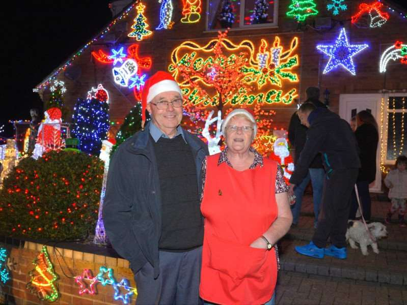 Helen and John Attlesey outside their Soham home with its huge display of Chritsmas lights