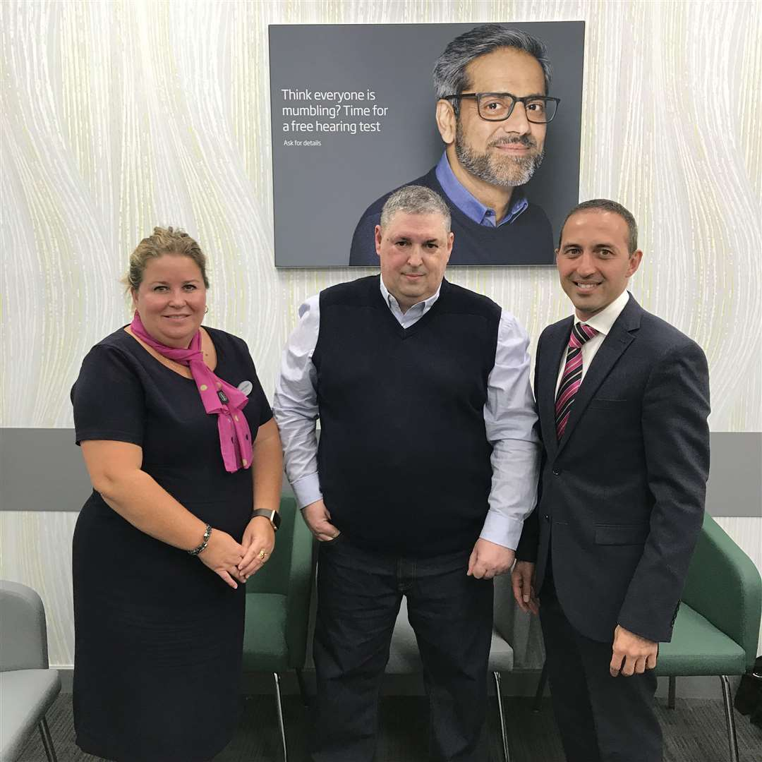 Sudbury resident Phil Cottage backs National Eye Health Week, after a tumour was found behind his eyes following a test. Pictured: Phil Cottage (centre) with Specsavers Sudbury retail director Lynette Copeland and optometrist Naeem Kazi. (4432029)