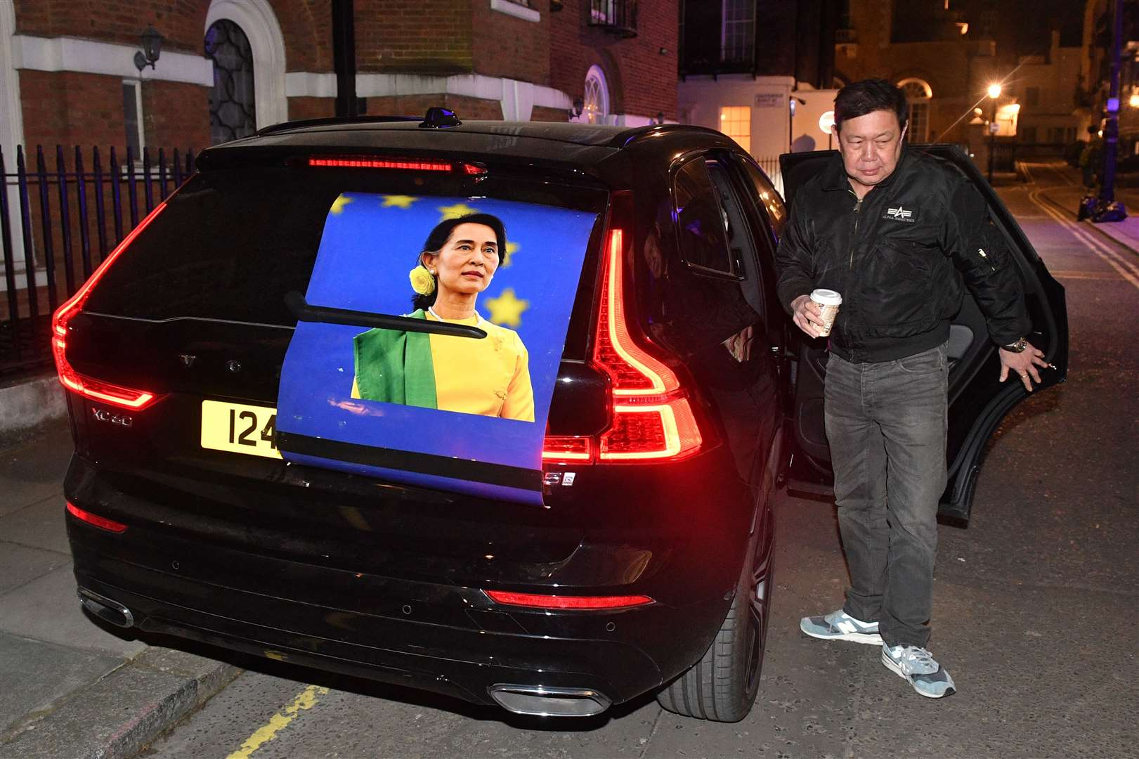 Kyaw Zwar Minn next to a car bearing the opposition leader's image (Dominic Lipinski/PA)